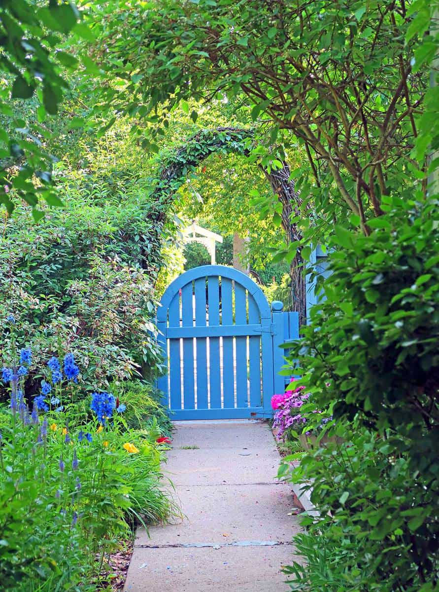 Arched blue garden entrance gate with summer flowers