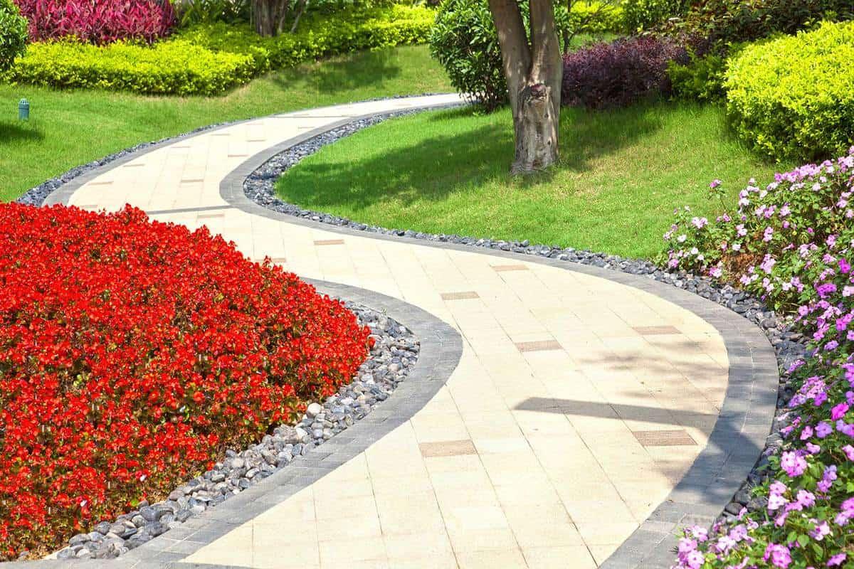 Bright summer garden planted alongside winding tile walkway