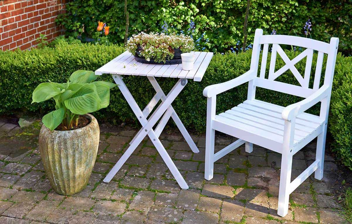 Garden corner with white chair and table