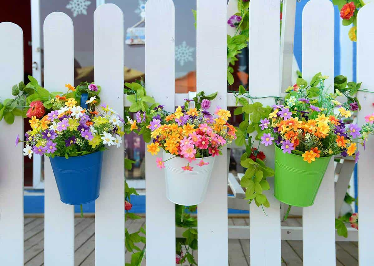 colorful hanging flower pots with white fence