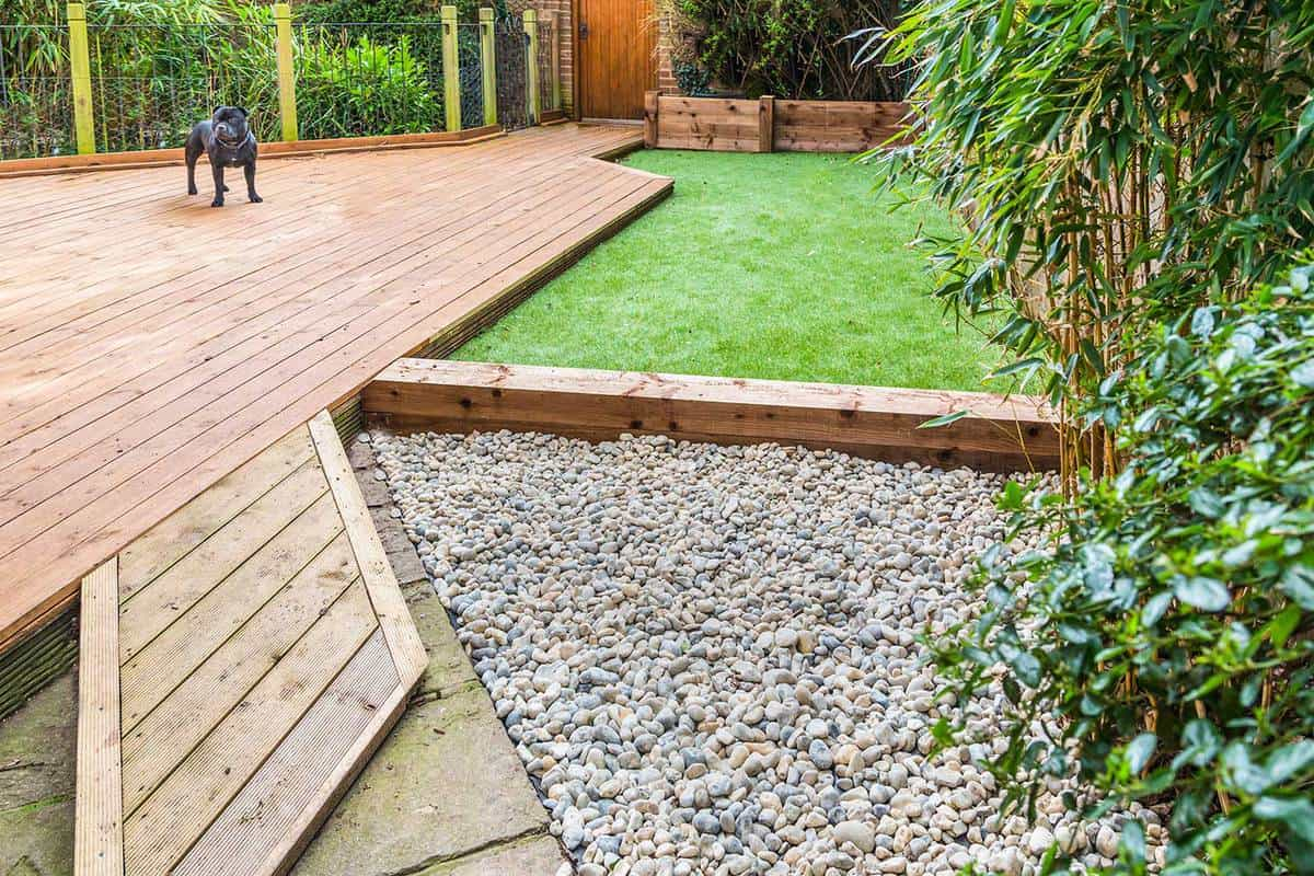 Section of a residntial garden yard with wooden decking and artificial grass