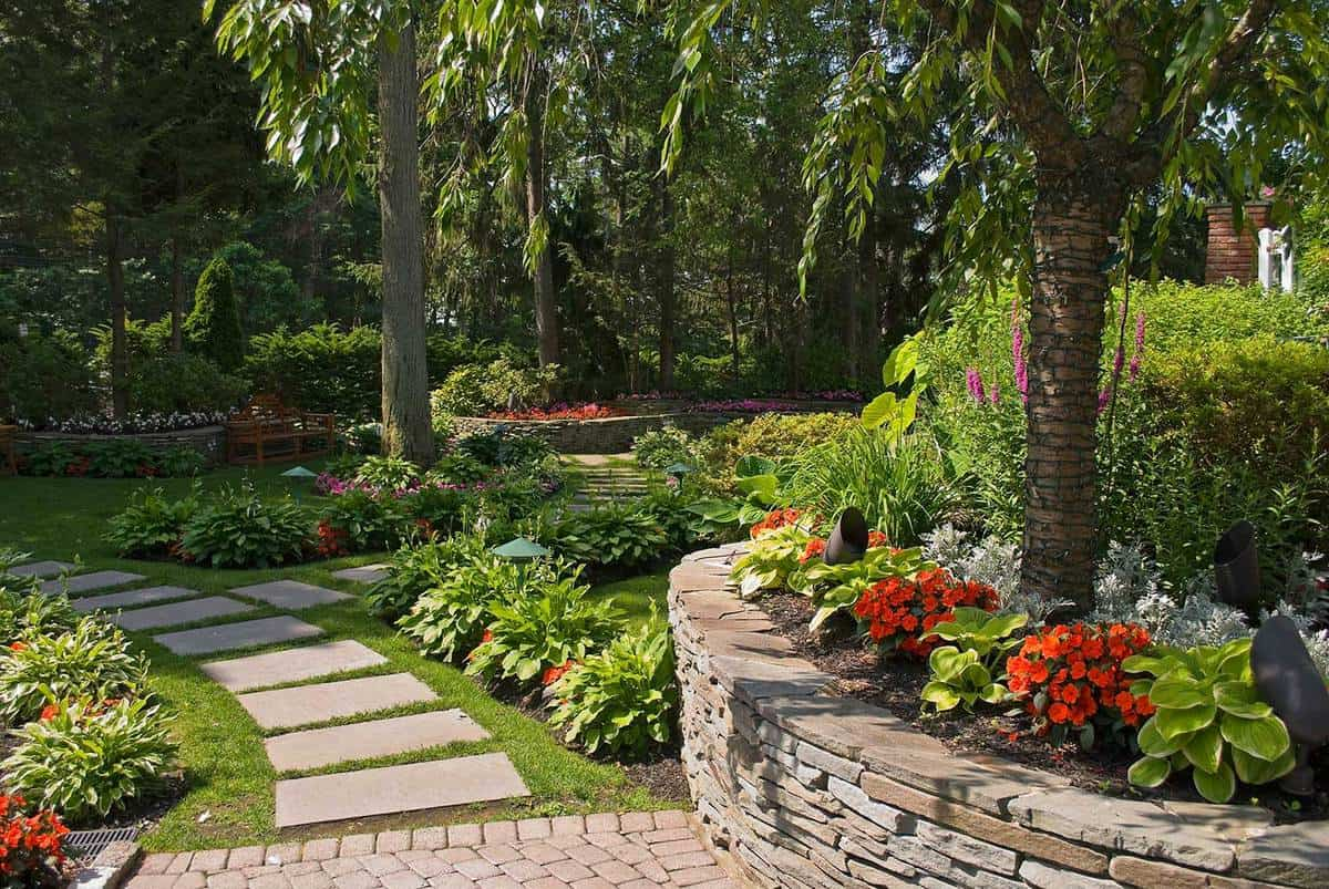 Summer garden with stone wall and path