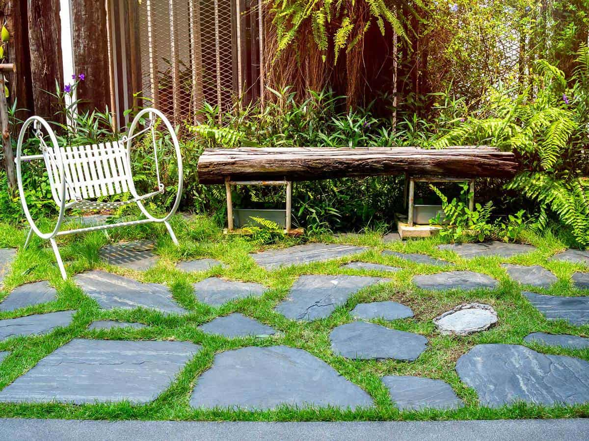 White vintage garden swing seat on stone floor