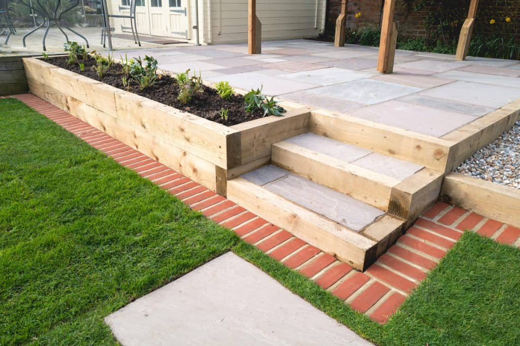 A garden with a wooden planter and a brick edging with bermuda on the side