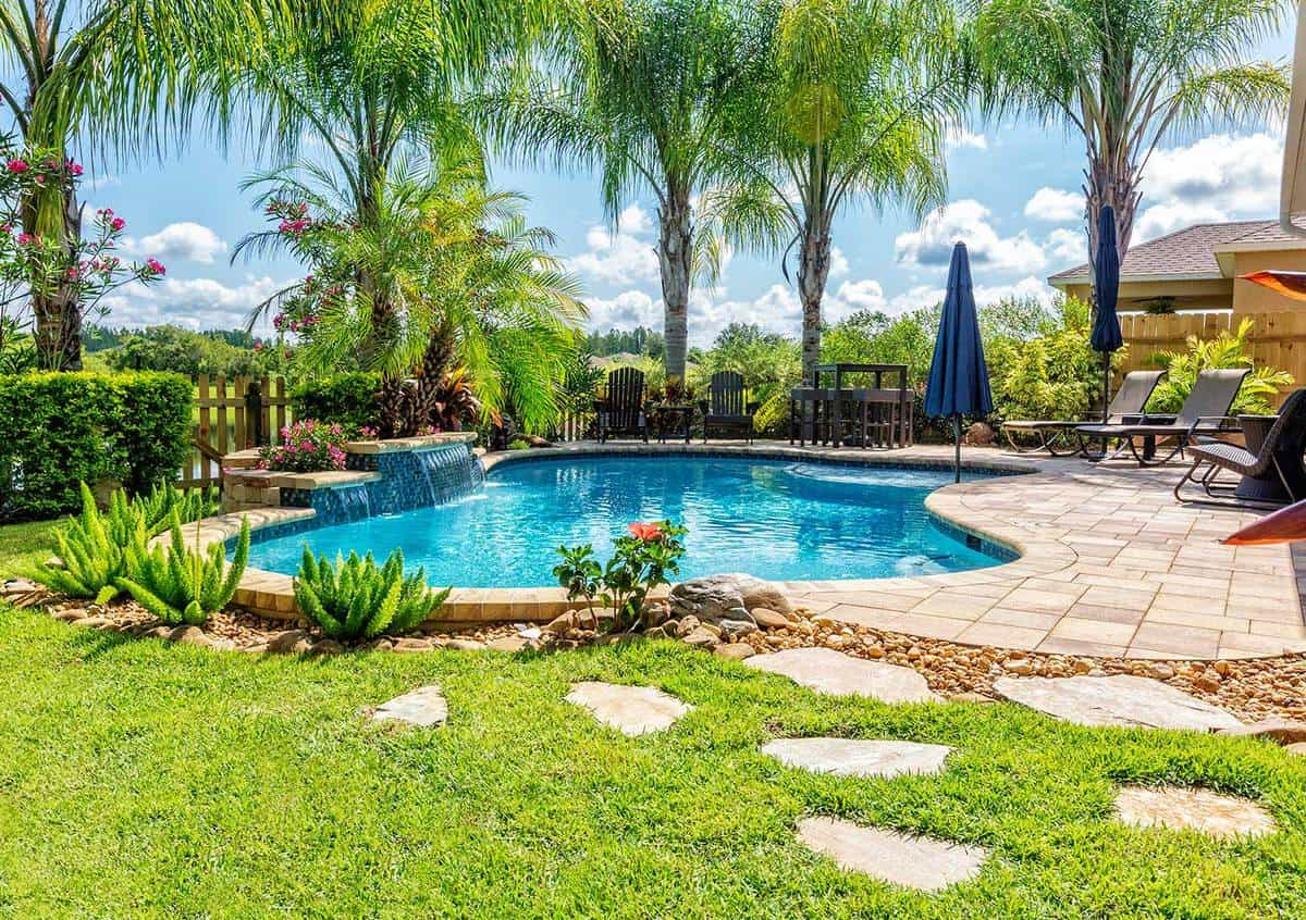 A beautiful backyard swimming pool in Florida surrounded with palm trees