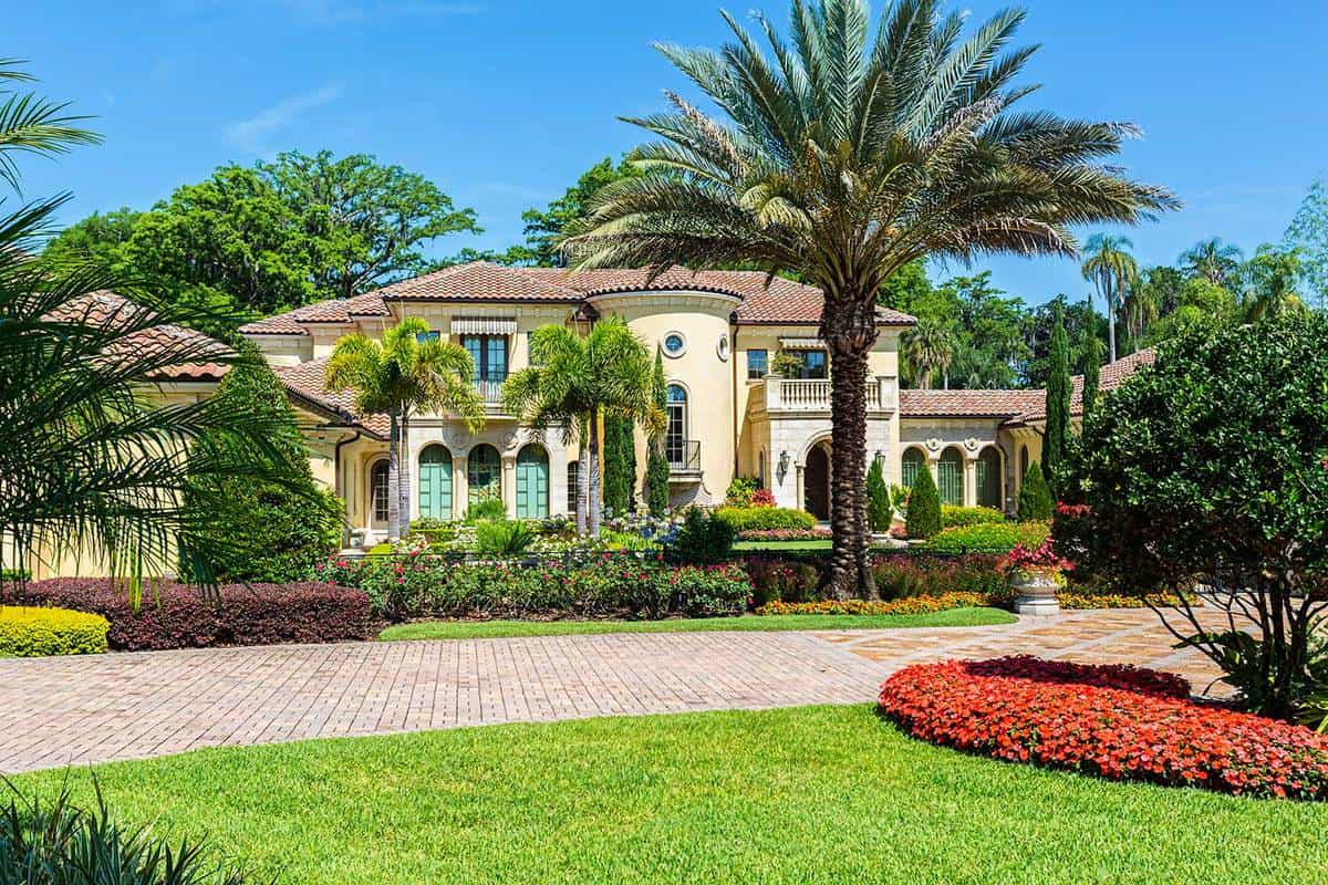 A beautiful estate home with palm trees on a landscaped front yard