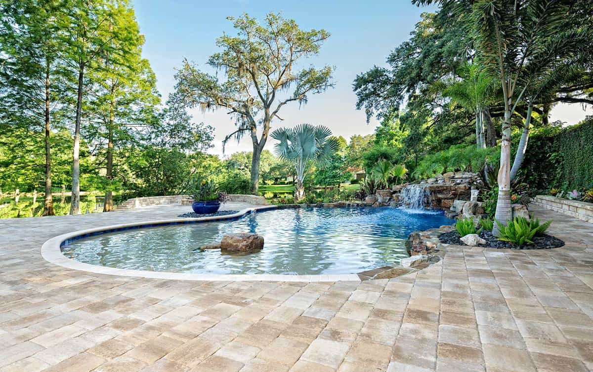 A beautiful landscaped swimming pool with waterfall at an estate home overlooking a lake in Florida