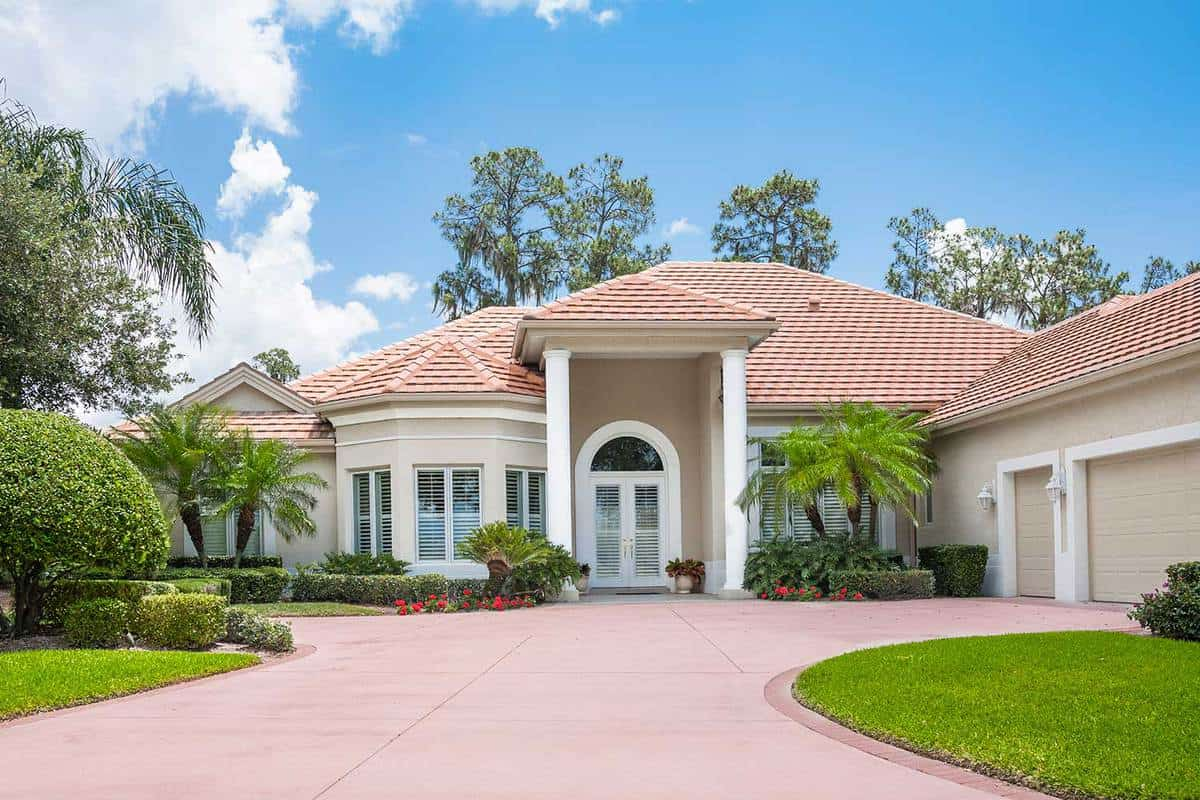 Beautiful new upscale home with palm trees, shrubbery, flowers, and wide driveway