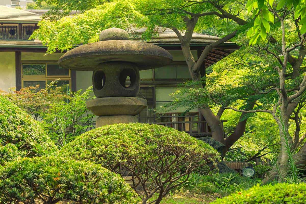 Big stone lantern in japanese zen garden by summer time