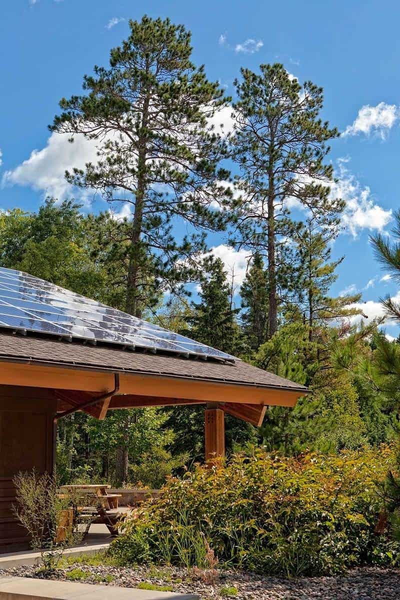House with solar panels on the roof surrounded by pine tress