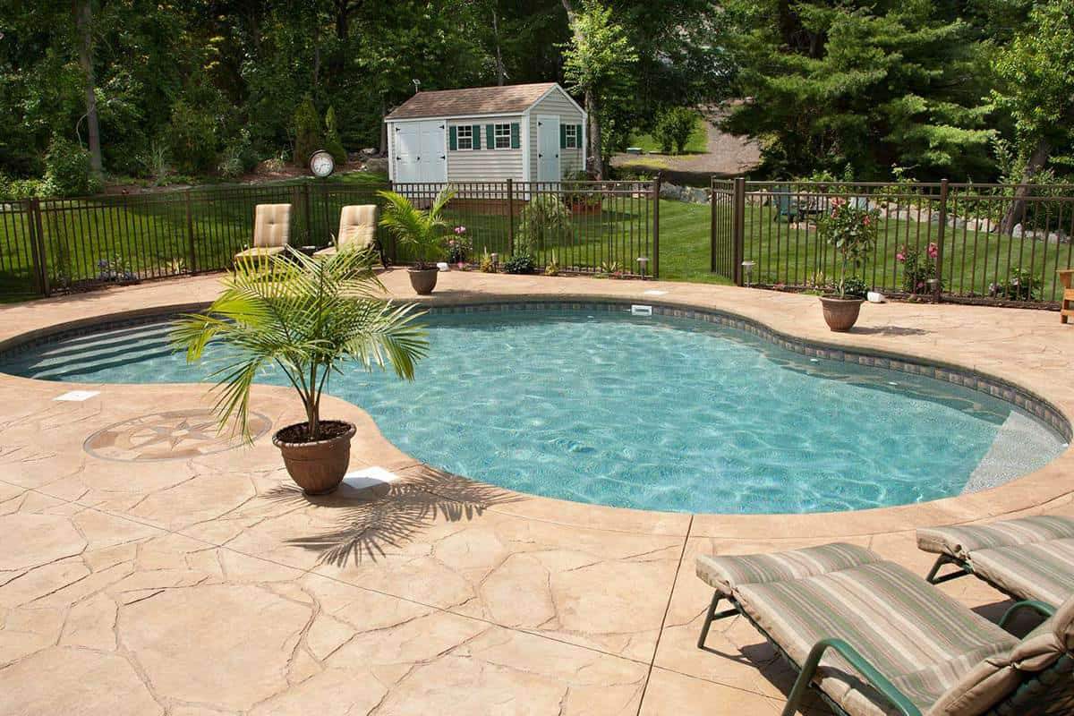 Lush, resort-like backyard salt water swimming pool with flagstone stamped concrete patio