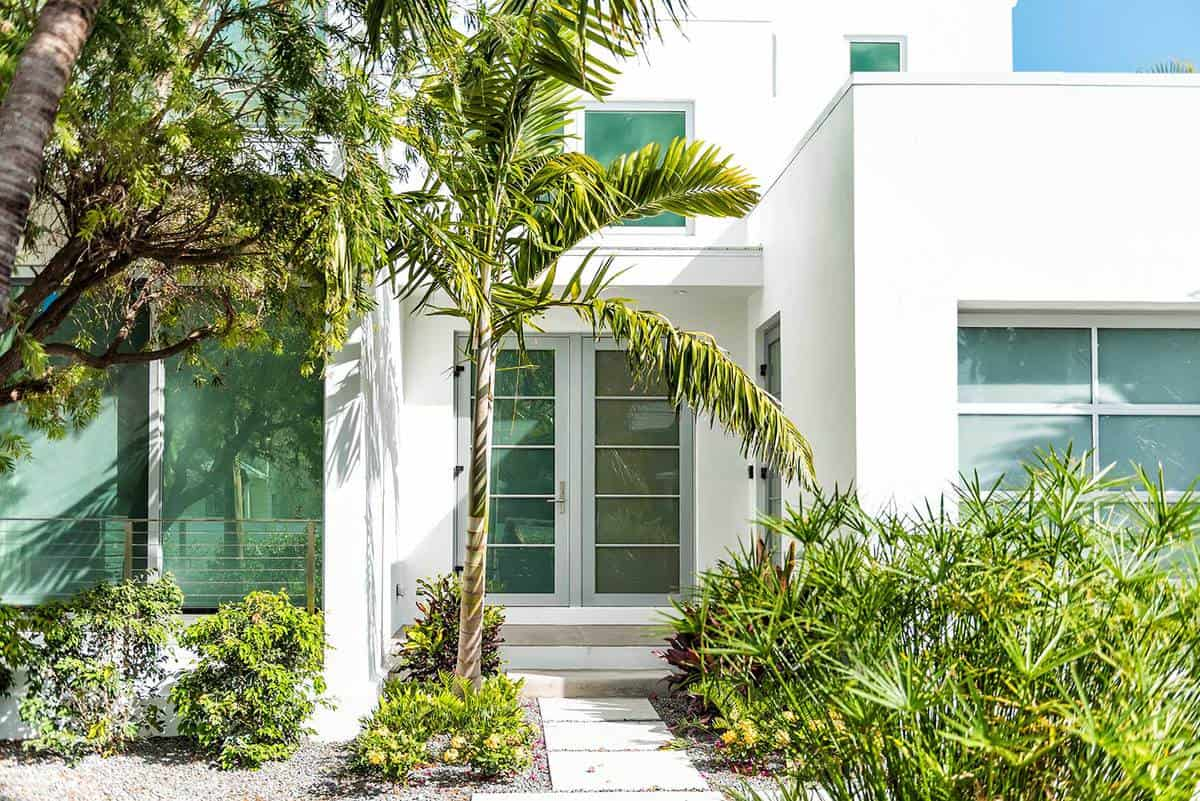 Luxury modern entrance of a estate house in Florida with garden landscaping decoration and green glass windows