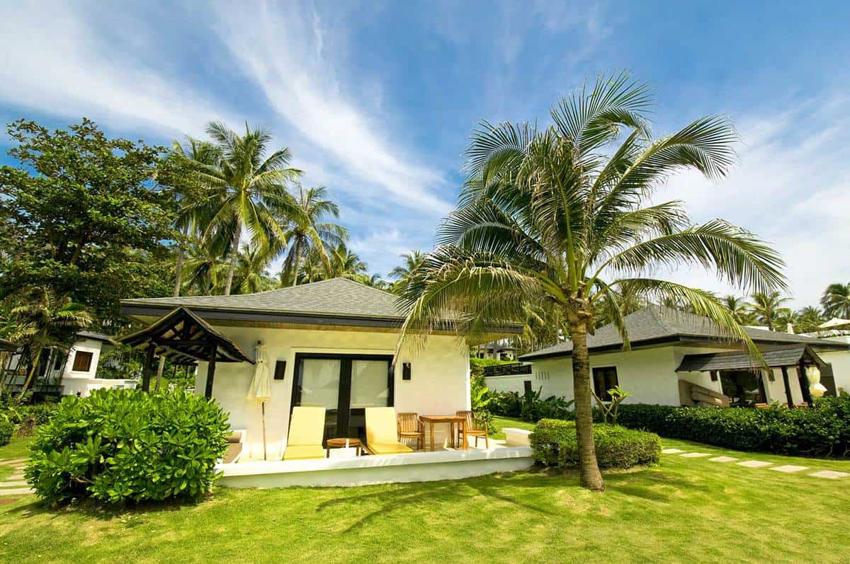 Modern luxury and exotic villa in a tropical island with palm trees and green grass on the yard