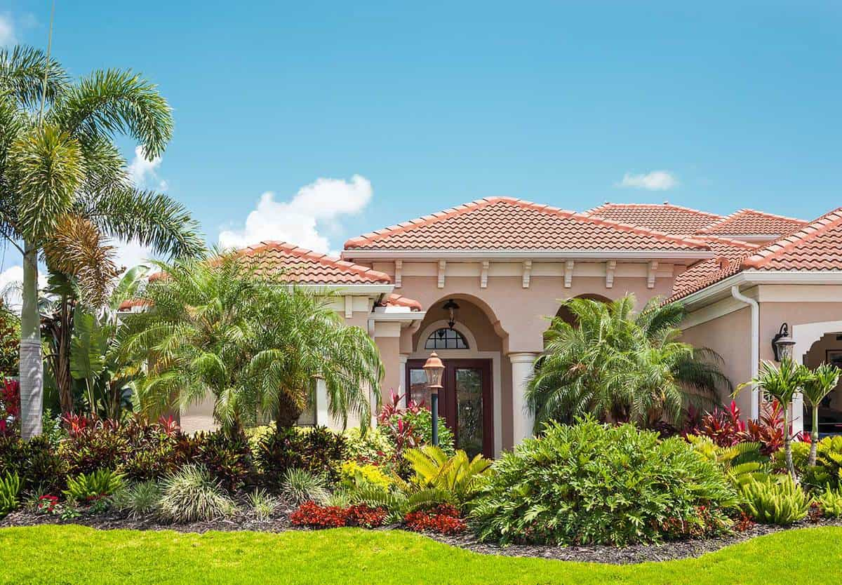 New luxury home with lush tropical foliage palm trees, flowers, tropical plants and bushes