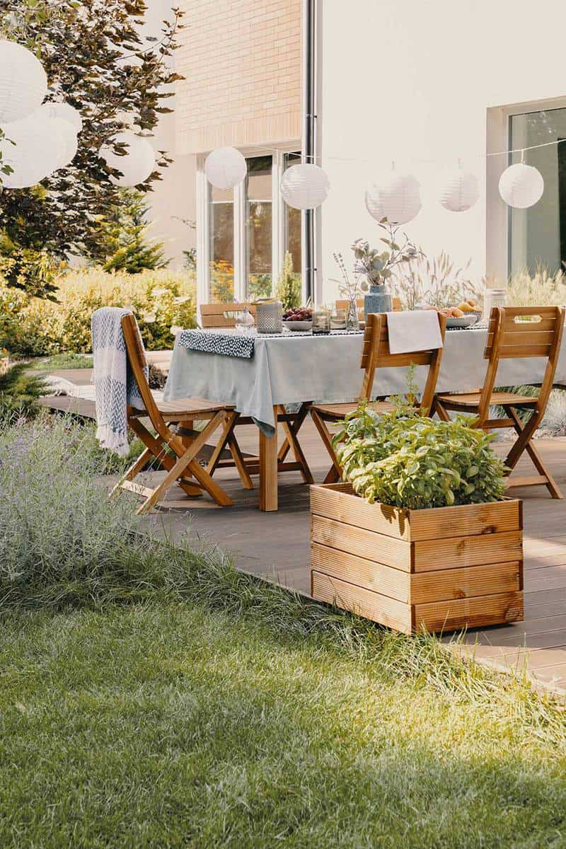 Patio garden with table, chairs, lamps and wooden planter box