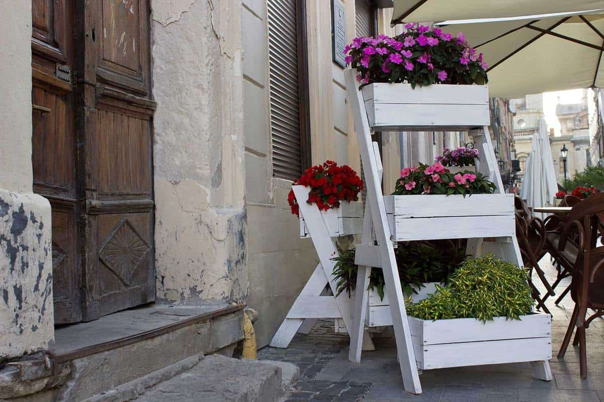 White planter boxes with flowers on the street near cafe