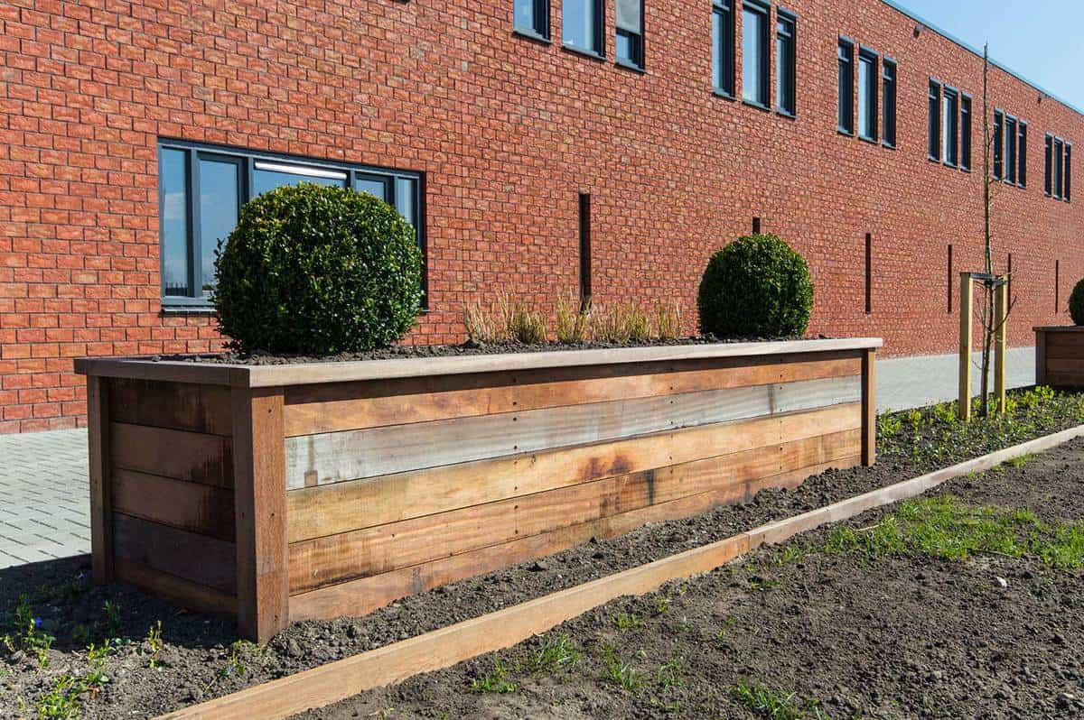 Wooden garden bed in front of a new building