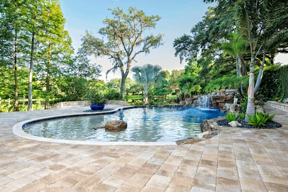 A beautiful landscaped swimming pool with good trees around, and a waterfall at an estate home overlooking a lake in Florida