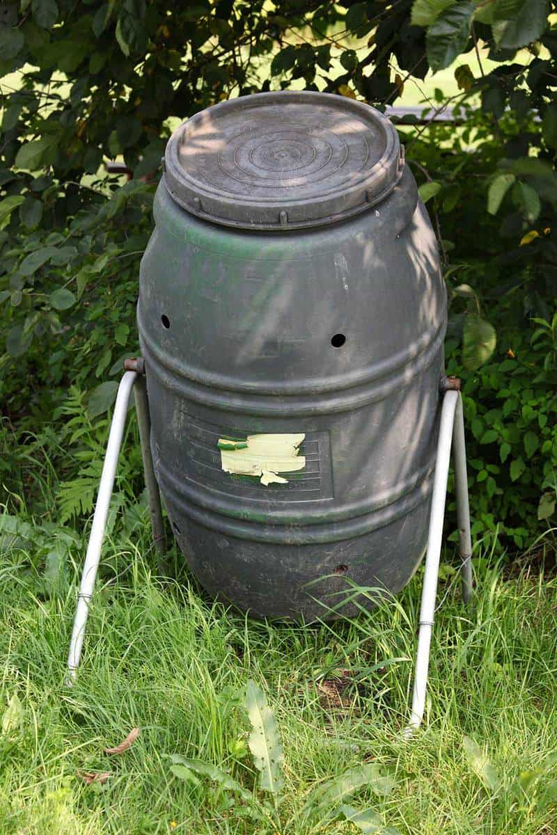 Compost tumbler on grassy yard