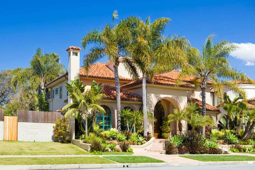 Palm trees in front of huge white mansion in southern california