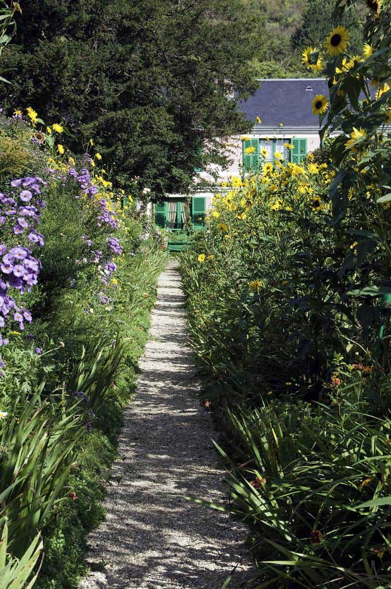 Gravel path leads through a rustic cottage garden to a French country house
