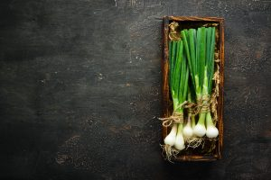 Grow onions placed on wooden container, How To Grow Green Onions Indoors?
