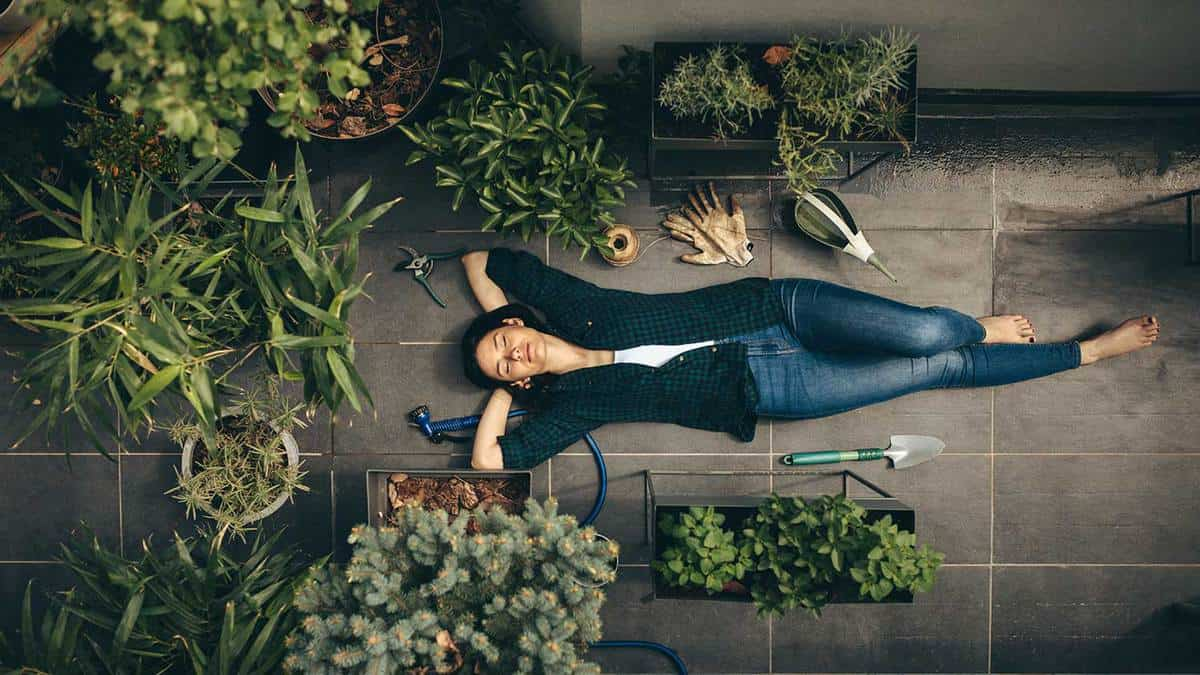 Young woman lying in her rooftop garden having a rest from gardening