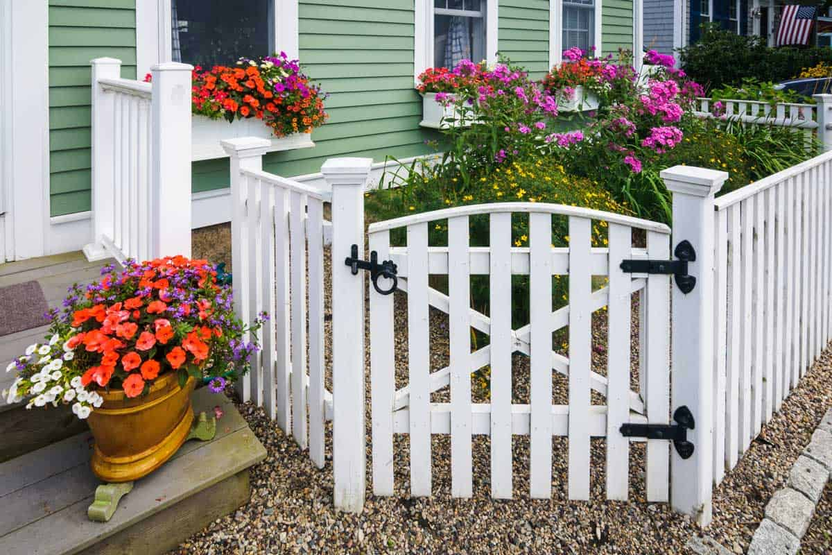 With limited space available, this home owner created an attractive pocket garden behind the gate, overflowing window boxes, and a pot of color on the steps.