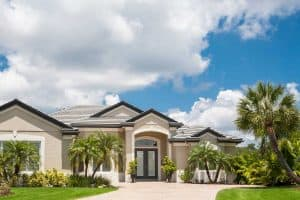 New luxury home in the tropics with driveway, palm trees, lush tropical foliage, front lawn in Florida, 15 Best Palm Tree Insecticides That Can Save Your Trees