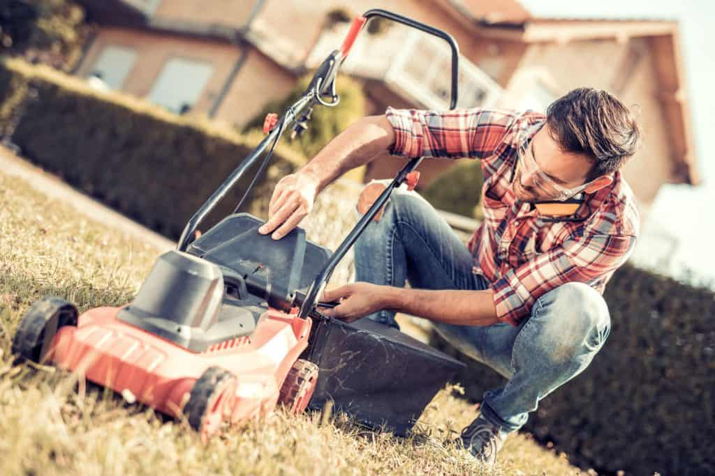 A checking his lawn mower before starting it