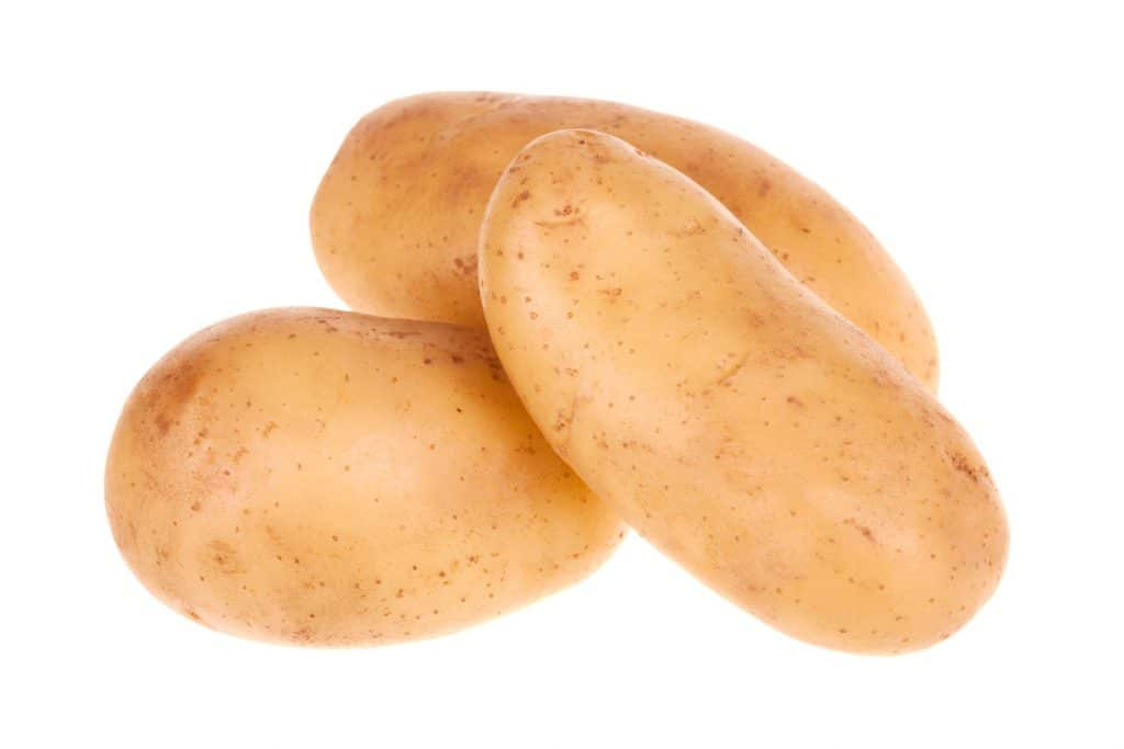 An up close photo of three potatoes on a white background