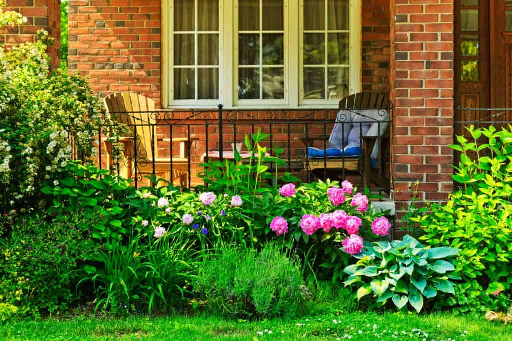 A brick front porch with a garden with lots of flowers