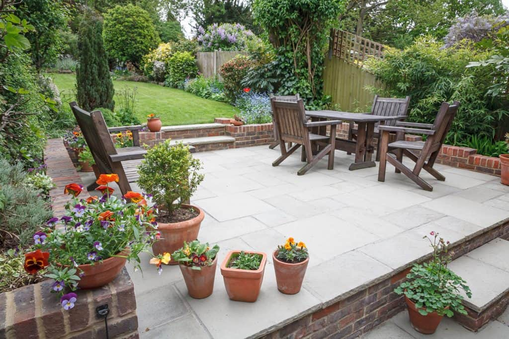 A large and spacious garden area with a patio designed with small garden pots and beautiful flowers