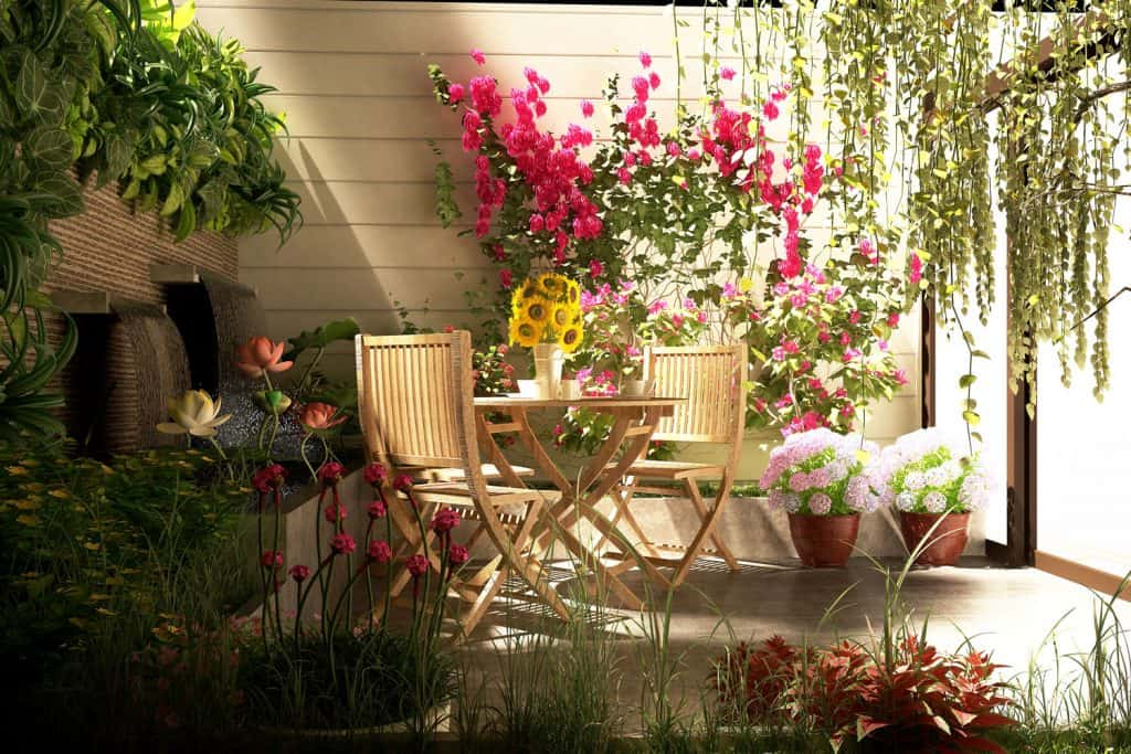 A small stunning garden area decorated with flowers making a perfect resting place