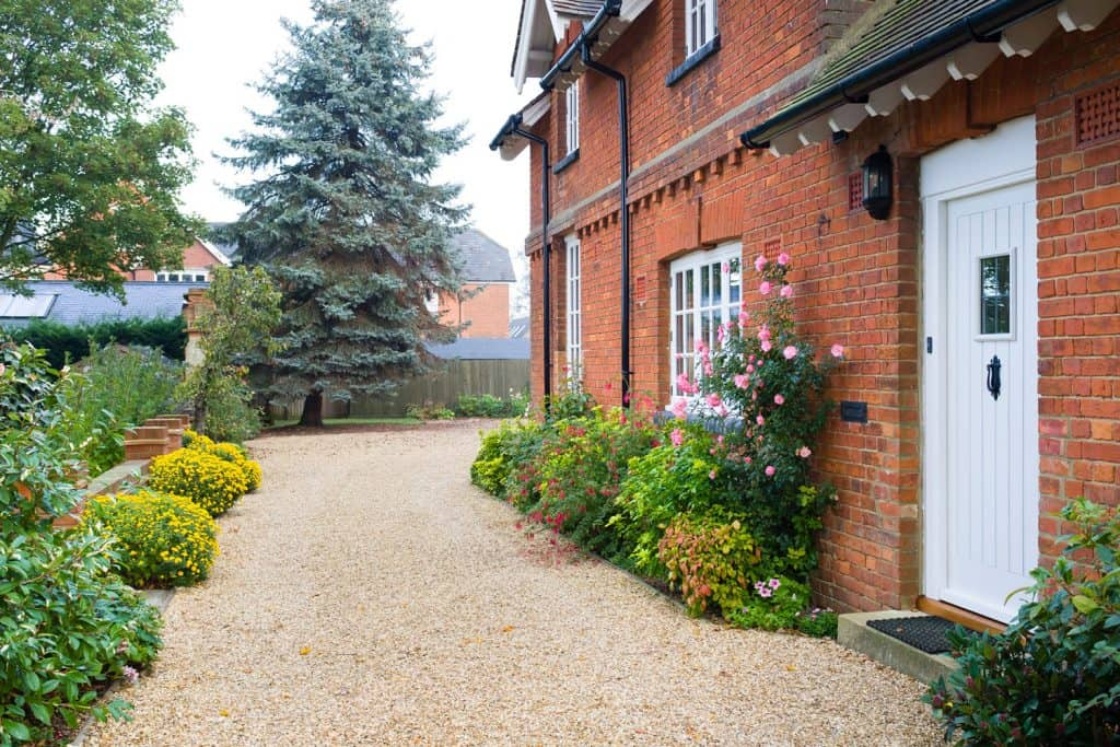 Exterior of a brick house with a small sand pathway with flowers and plants on the sides