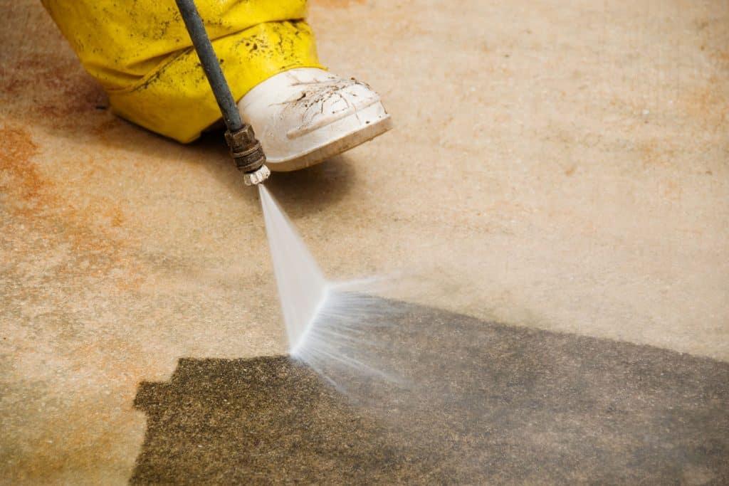 A man using a power jet sprayer to clean the garden pavement