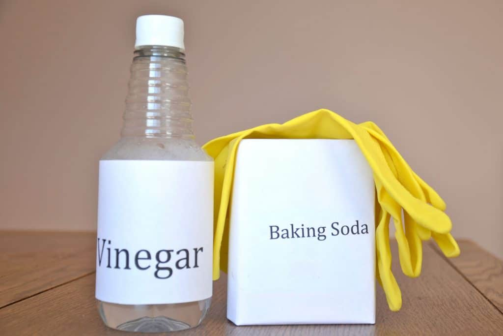 A small bottle of vinegar and baking soda with a small yellow glove on top