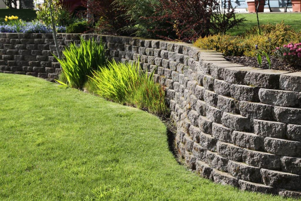 A retaining wall decorated with decorative rocks on the backyard garden