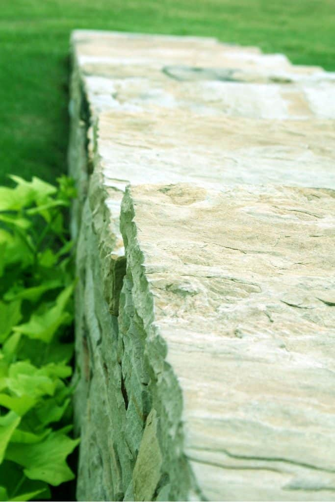 A retaining wall made out of decorative stones and plants on the front
