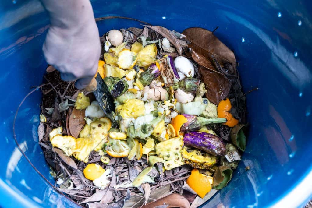 A woman wearing gloves and mixing the compost bin