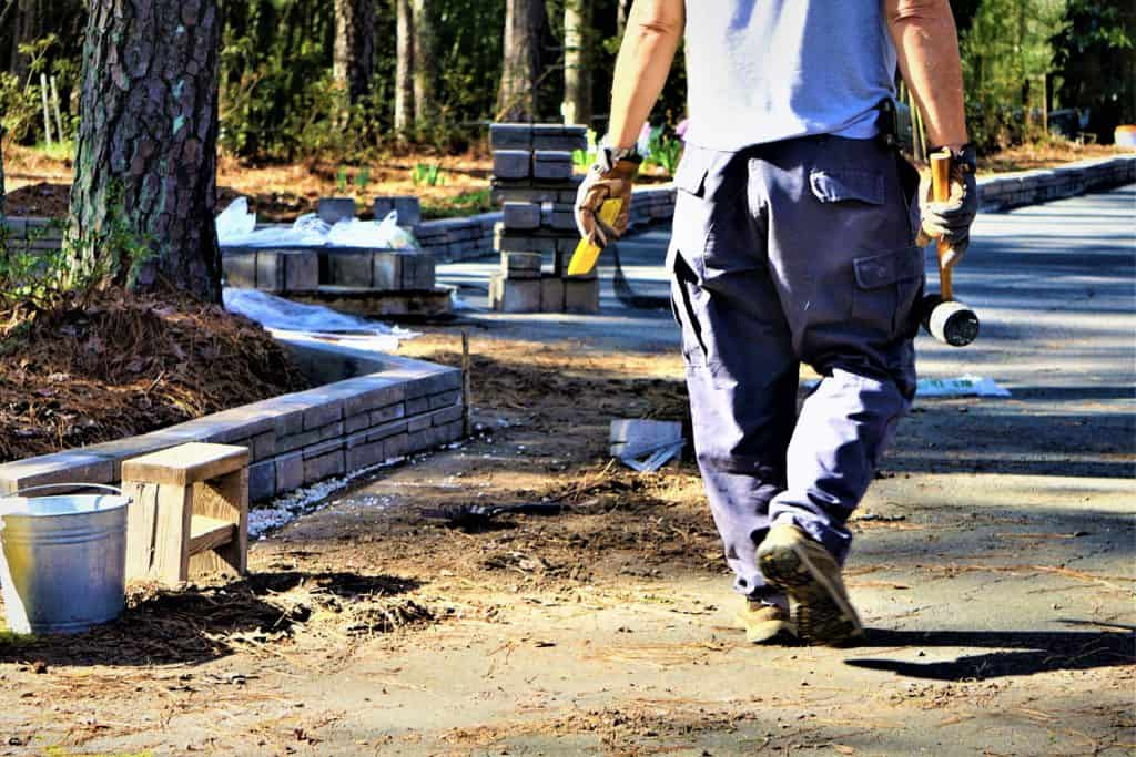 A worker carrying masonry materials for a retaining wall