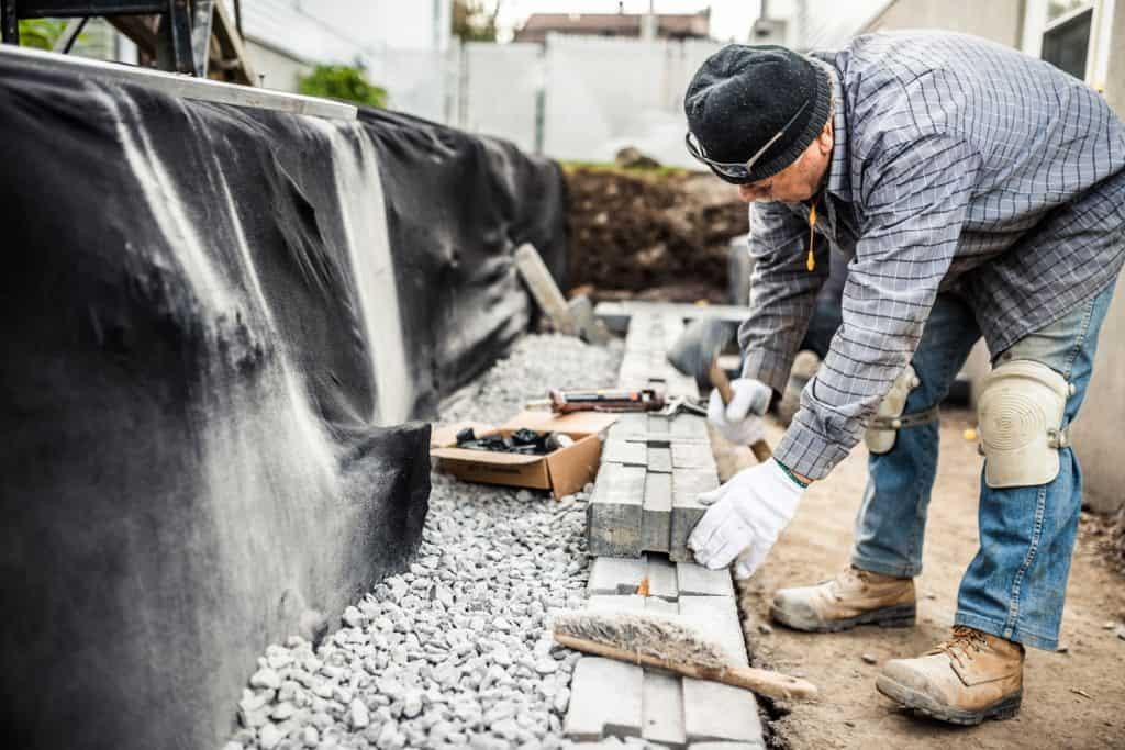 An elderly man making forms for the retaining wall