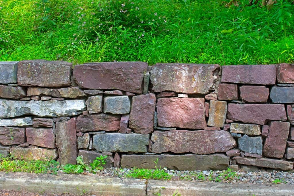 Retaining wall of various shaped stones holding up a sloped and grassy hill