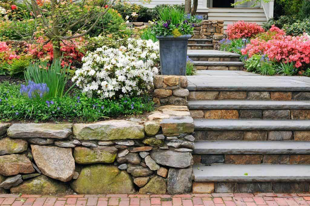 Stone wall on a colorful garden