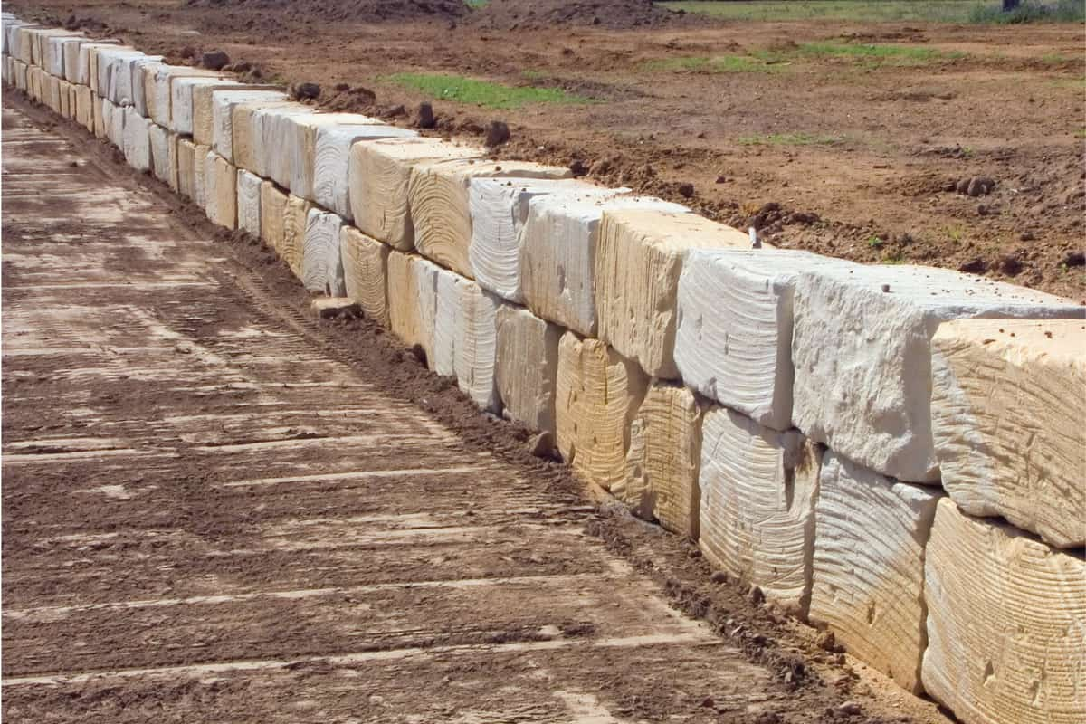1 ton sandstone blocks fashioned into a long retaining wall during landscaping at a new estate