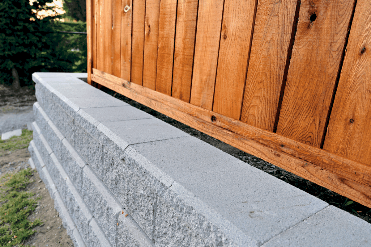 A beautiful close-up look at a residential cement block retaining wall with a wooden fence build behind as an aesthetically and safety upgrade option.