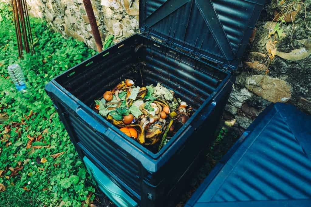 A big black compost bin with lots of vegetable left overs and vegetable peels