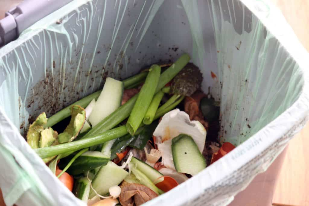 A garbage bin filled with vegetable peels and other leftovers