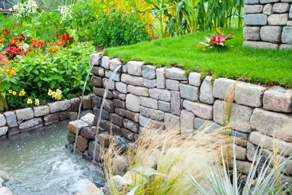 A gorgeous retaining wall made from selected square rock with tow small water sprouts for irrigation