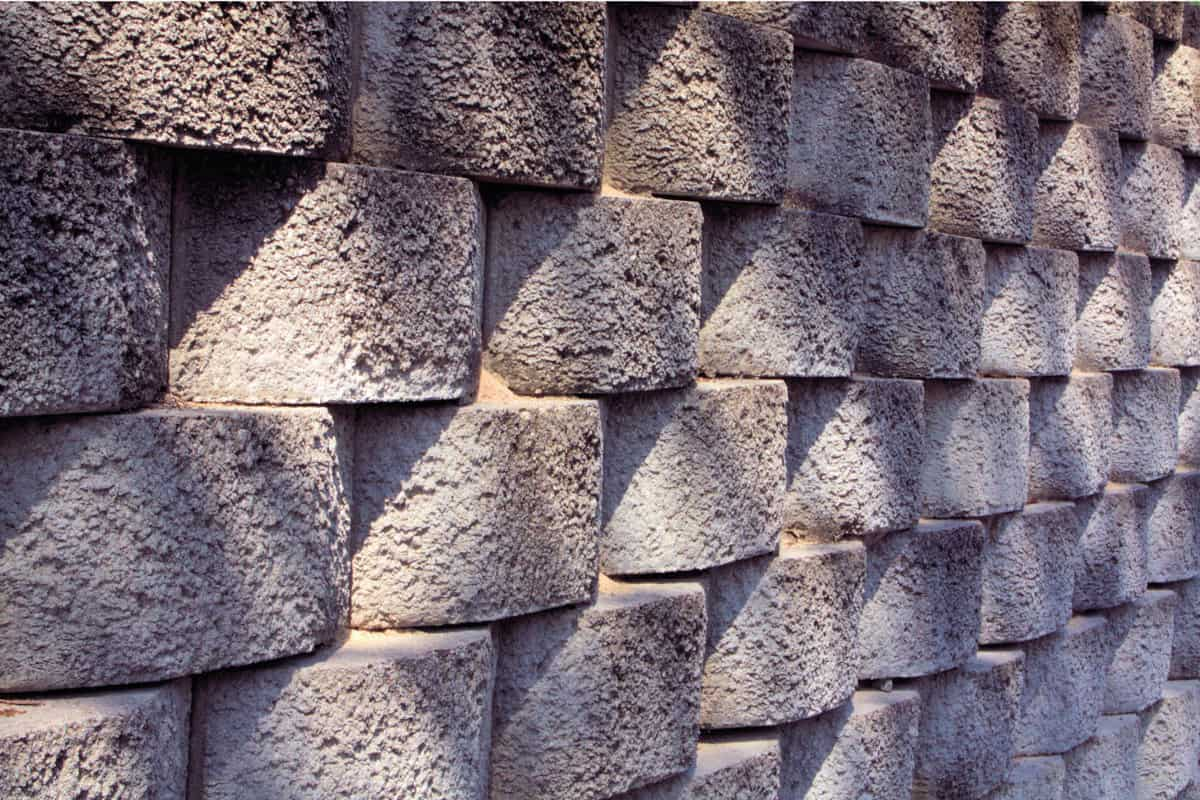 A patterned and rough looking concrete block retaining wall.